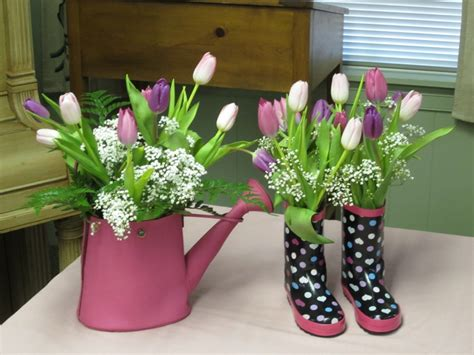 watering can centerpieces tulips and babies breath in watering can and galoshes centerpieces centerpieces