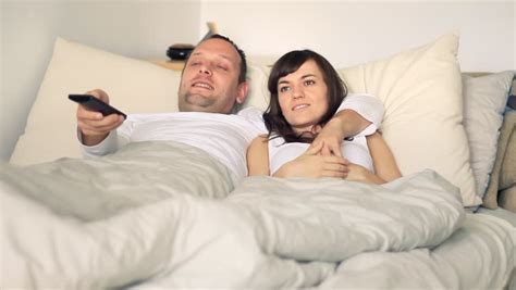 watching tv in bed young couple in bed watching tv stock footage video