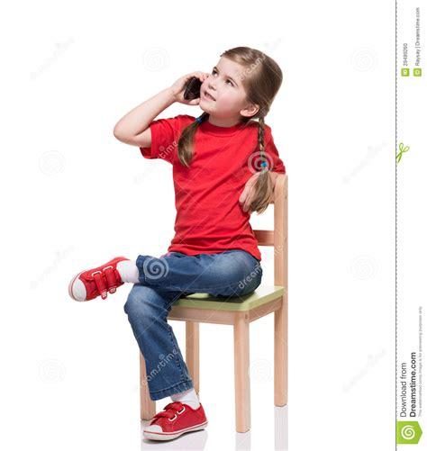 little girl on chair little girl sitting on a chair and speaking by smartphone