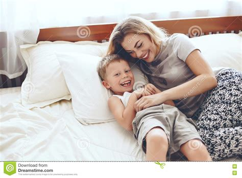 mother playing with son on bed in bedroom stock photo mother plays with son in bed stock photo image 70399730