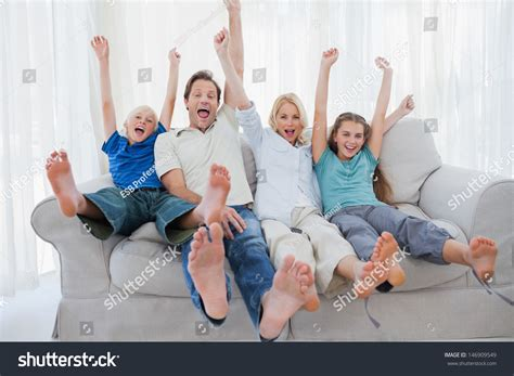 you sitting on the couch watching tv family sitting on a couch and raising arms while watching
