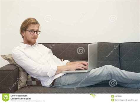 sitting on couch young man sitting on couch with laptop stock photo image