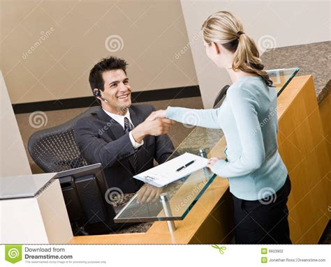 Receptionist Greeting Woman At Front Desk Stock Photo