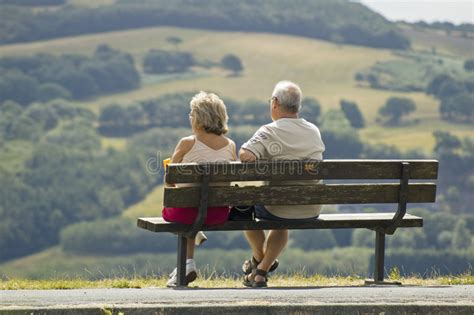 two people sitting on a bench two older people sitting on a bench stock photo image of