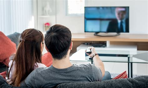 asian family watching tv together in living room this is tv remains top media channel in hong kong nielsen
