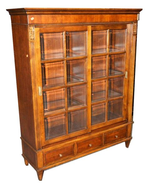 a ethan allen walnut finish 2 door bookcase with sliding m02
