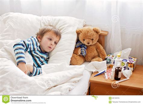 sick bed sick child boy lying in bed with a fever resting stock