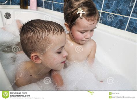 girl in bathroom with boy brother and sister taking a bubble bath little boy and