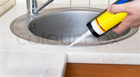 plumber putting a silicone sealant to installing a kitchen