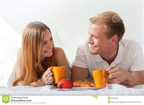 eating in bed couple chatting and eating in bed stock photo image