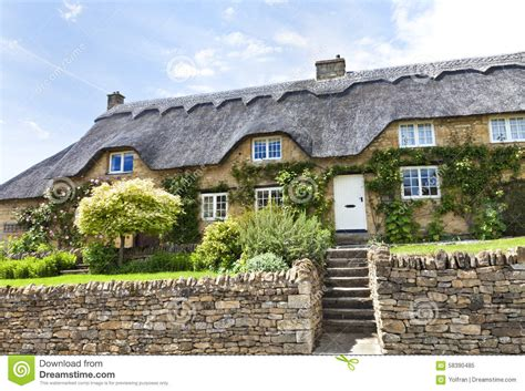stone thatched cottage with flowers stone wall stock