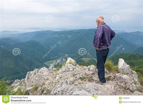 man standing on mountain top senior man standing on top of a mountain royalty free