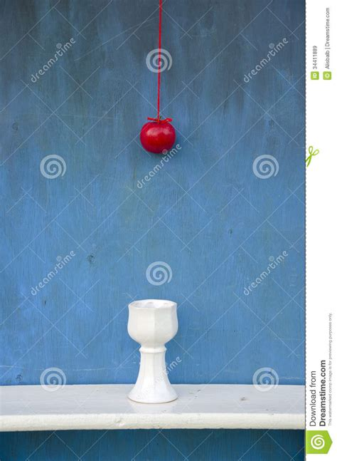 hanging red apple on string and white vase royalty free
