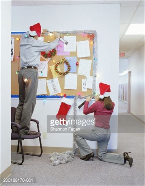 businesspeople putting up christmas decorations in office