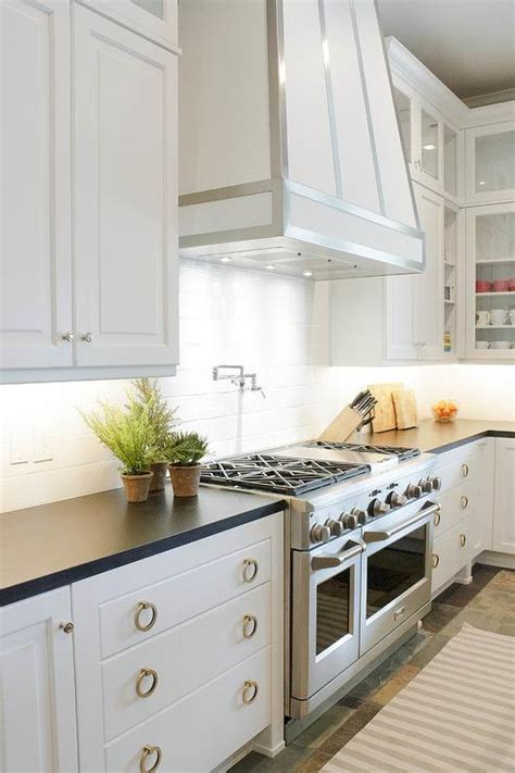 small white kitchen with steel hood white upper kitchen cabinets with taupe lower kitchen