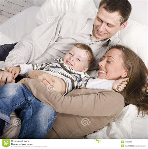 mom son bed portrait of happy family mom and dad playing with their