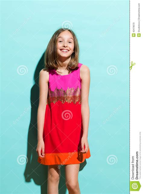 small teen smiling girl on turquoise background stock photo image