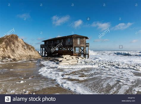 nags house house on stilts surrounded by high tide surf nags