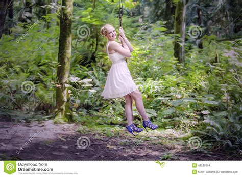swinging girl girl swinging in forest stock photo image 49229304