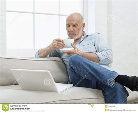 mature sofa mature man with laptop and coffee cup on sofa royalty free