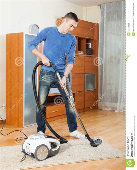cleaning with vacuum cleaner in living room stock