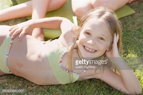 young girls swimwear age 13 girl lying on grass in bikini smiling portrait stock photo