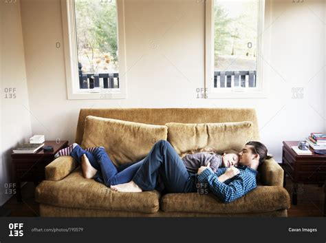how to cuddle on a couch couple cuddling and sleeping on couch together stock photo