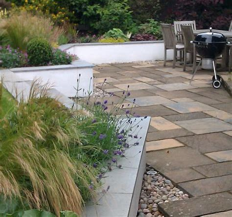 Interesting Angles back garden seating area with steps to lawn greenspace