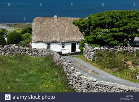 white washed thatched cottage with dry stone walls and