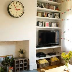 Photos and books displayed on alcove shelving plus a retro wall clock