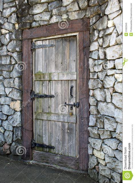 porta di legno porta di legno antica in una parete di pietra fotografia