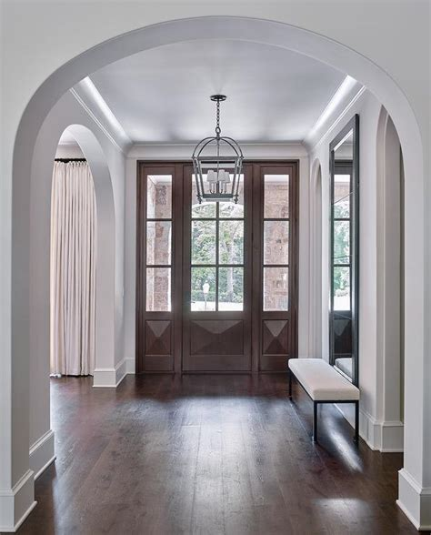 Foyer With Grey Grasscloth And Board And Batten Front Door Mirror