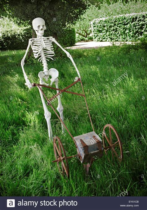 overgrown garden sculpture of skeleton mowing grass in an overgrown