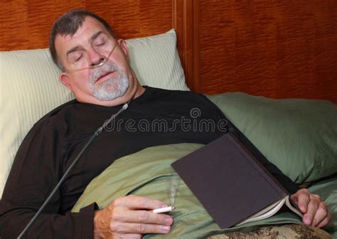 smoking in bed man with oxygen cannula smoking in bed stock photos