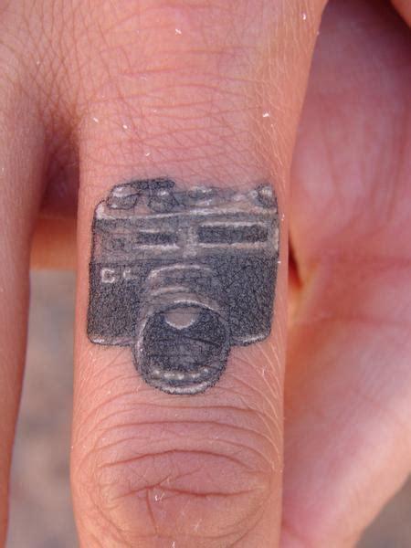 realistic tattoo generator miniature camera on finger by mario sanchez tattoos
