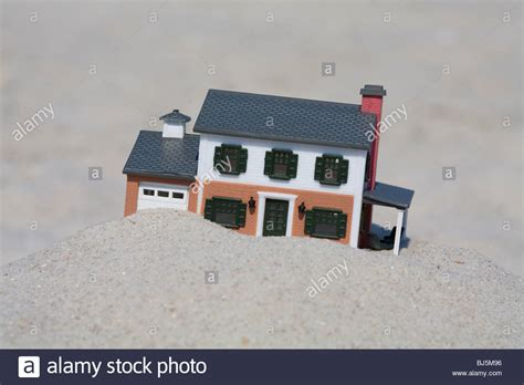 buying a house with another person only a foolish person would build a house on a weak sandy foundation stock photo