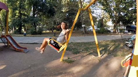 motion of a child on a swing is child riding on a swing at the playground stock footage