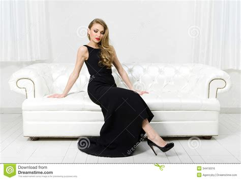 sitting in sofa woman sitting on white leather sofa royalty free stock