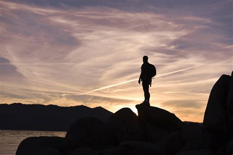 man standing on mountain top silhouette photo on man standing on top of mountain free