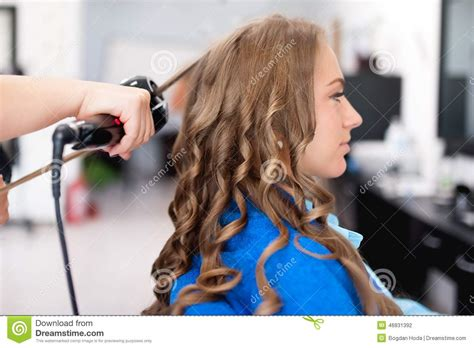 how stylist curled your hair in the 50s and 60s professional hairdresser using curling iron for hair curls