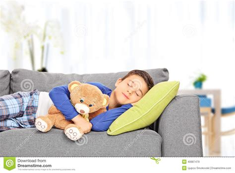 little kids couch little kid sleeping on sofa with a teddy bear at home