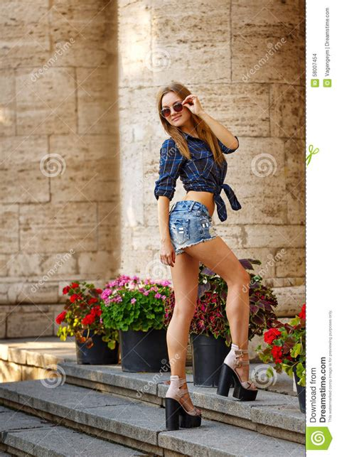 hipster girl  shirt  jeans shorts climb stairs stock