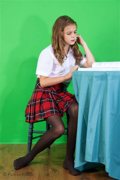 preteen nylon young girl in school outfit studies at a small table