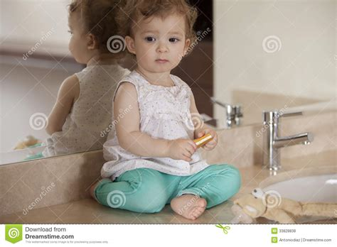 girl has baby in bathroom waiting for mom to get ready stock photo image 33828838