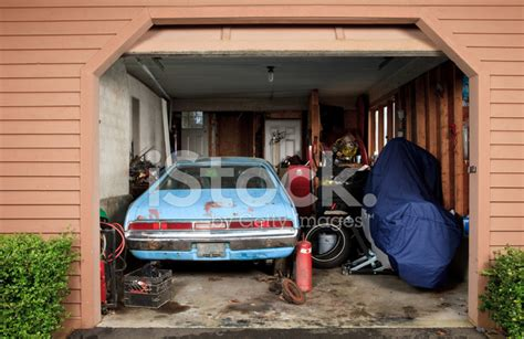 Single Car Garage Size Small Garage Filled With A Car Motorcycle And Tools Stock