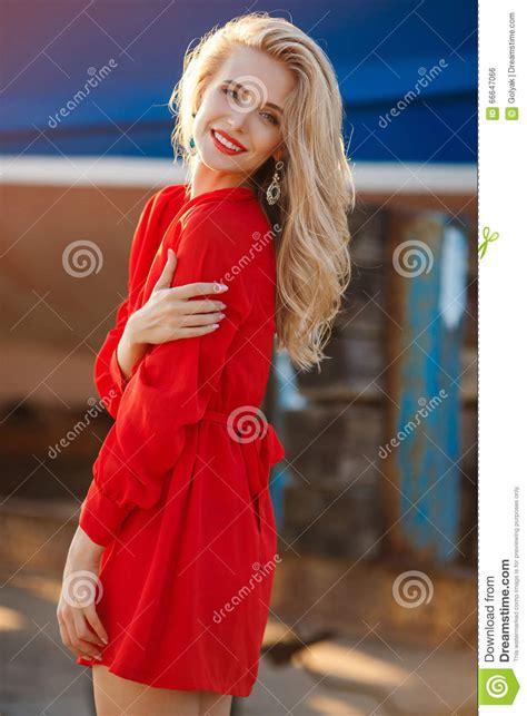 blonde bob red dress portrait of beautiful women in old dock stock photo