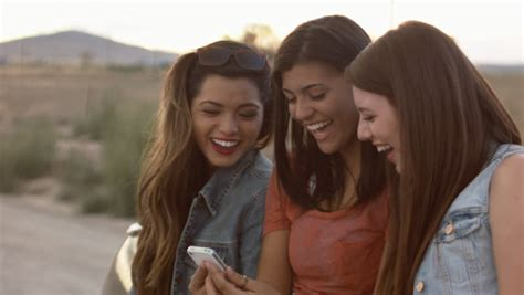 group teen girls laughing multi ethnic group of teen girls laughing at a phone