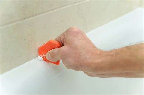 worker smoothing silicone sealant len  plumber