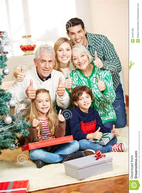 family at christmas holding thumbs stock photo image
