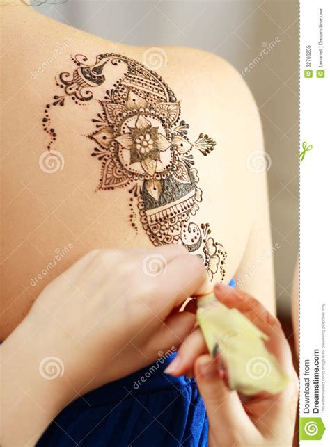 process of applying henna tattoo mehendi on the henna applying on the back royalty free stock photo